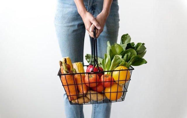 Žena, ktorá v rukách drží košík plný ovocia