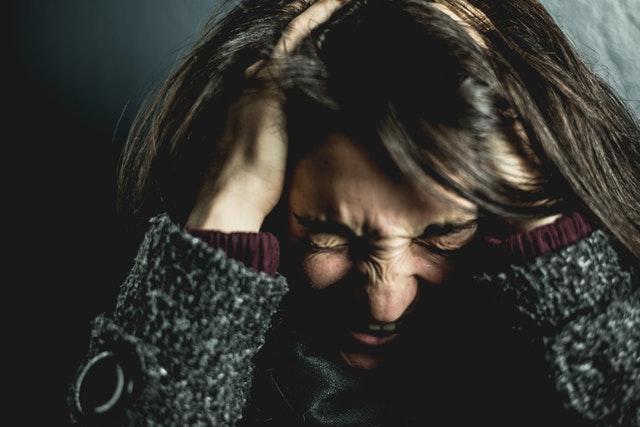 Nervózna žena držiaca sa za hlavu