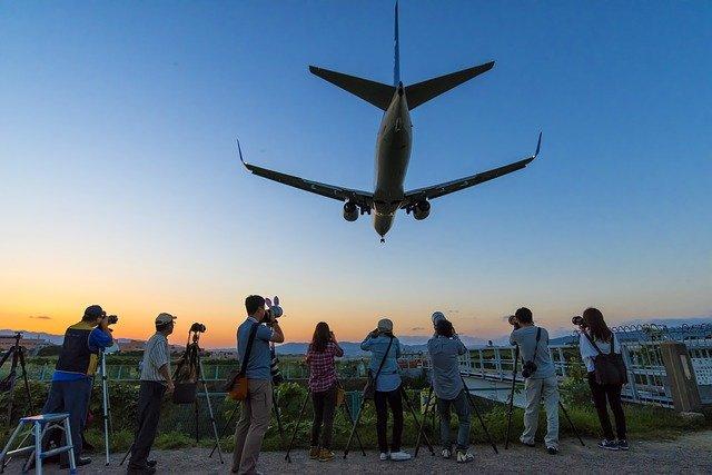 Ľudia fotia lietadlo vo vzduchu.jpg