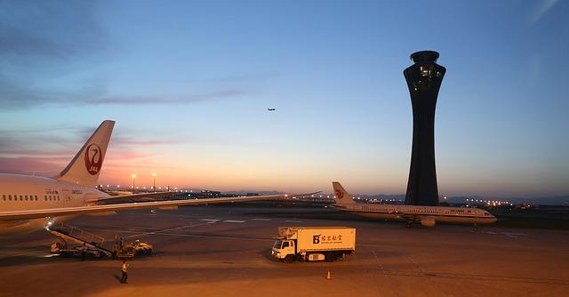 Dve lietadlá a nákladné auto na letisku v noci.jpg